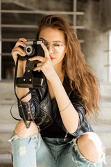 Photo of young cheerful woman in fashion transparent glasses wearing a rock black style leather jacket taking photo on vintage film camera. Hipster urban style girl. Lifestyle outdoor portrait.