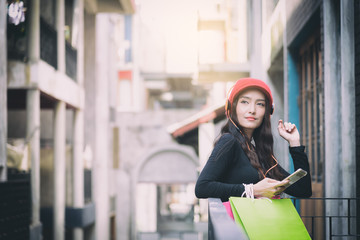 Asian portrait girl has happy and listening music with shopping colorful bags.