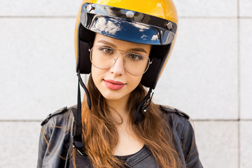 Close up portrait of beautiful woman in fashion glasses, rock black style leather jacket and glitter gold motorbike helmet look to camera. Hipster urban style girl. Lifestyle outdoor city portrait.