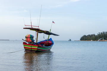 Small wooden tropical fishing boat on the beach with cloudy sky.