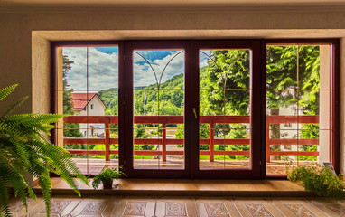 large glass doors in the house over which a panorama of mountains under the blue sky opens