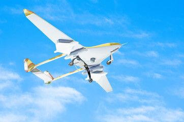 Unmanned aerial vessel is gaining altitude to track a mission against a blue sky.