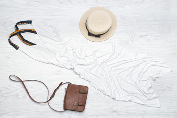 Fashionable concept. Female summer wardrobe. Straw hat, white sundress, handbag. Top view