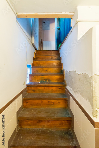 A Narrow Staircase In The Room Leading Up With Wooden Stairs