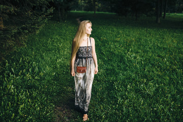 Attractive young girl with long hair in a beautiful outdoor dress