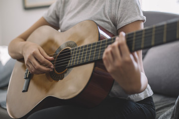 A young girl learns to play guitar. Woman's hands playing acoustic guitar.