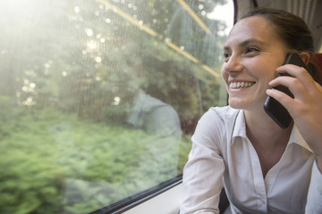 Businesswoman on the phone whilst travelling by train