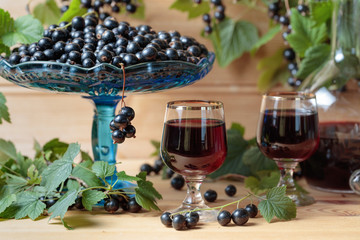 Homemade black currant liqueur and fresh berries .