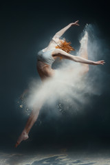 Dancing in flour concept. Redhead beauty female girl adult woman dancer in dust fog. Girl wearing white top and shorts making dance element in flour cloud in form of skirt on isolated grey background