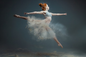 Dancing in flour concept. Redhead beauty female girl adult woman dancer in dust / fog Girl wearing white top and shorts making dance element in flour cloud in form of skirt on isolated grey background