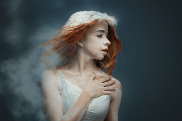 Dancing in flour concept. Cute fitness beauty redhead woman / female / adult dancer performer in dust / fog. Portrait of a girl dancer with ginger hair in flour on isolated backround