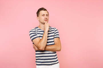 Portrait of handsome businesslike pensive young man in striped t-shirt put hand on chin copy space isolated on trending pink background. People sincere emotions lifestyle concept. Advertising area.