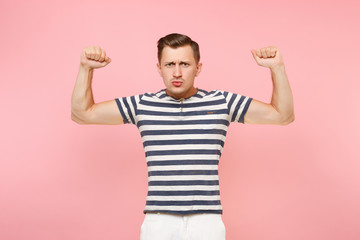 Portrait of strong young man wearing striped t-shirt man showing biceps, muscles on copy space isolated on trending pastel pink background. People sincere emotions lifestyle concept. Advertising area.