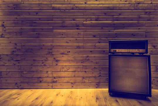 Guitar amplifier on wooden wall and floor, music studio