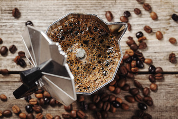 Moka coffee pot and coffee beans on wooden background