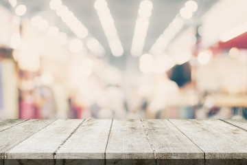 Empty wooden table and Blurred background - Store of shopping mall blur background bokeh with display montage for product.