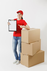 Full length of delivery woman in red cap, t-shirt isolated on white background. Female courier holding clipboard with papers document, blank empty sheet on empty cardboard boxes. Receiving package.