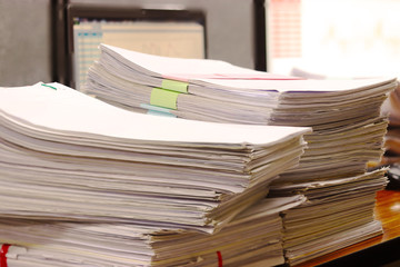 Close up pile of unfinished paperwork on office desk waiting to be managed. Stack of business paper. Report papers stacks. Business and finance concept.