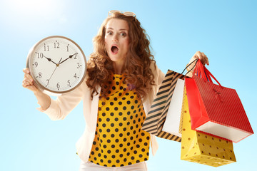 woman showing shopping bags and clock against blue sky