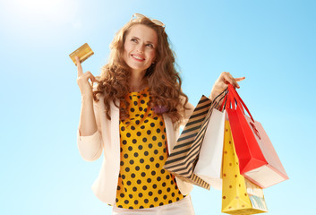 woman with shopping bags and credit card against blue sky