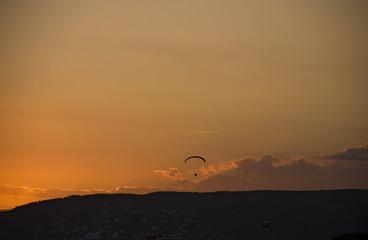 Gleitschirmflieger in der Abenddämmerung über Palamòs, Costa Brava, Katalonien, Spanien