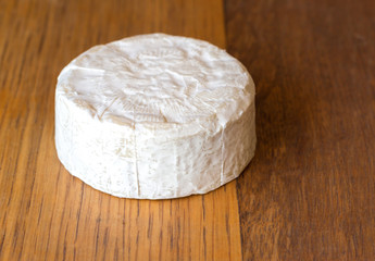 Camembert cheese round on oak wooden board close up