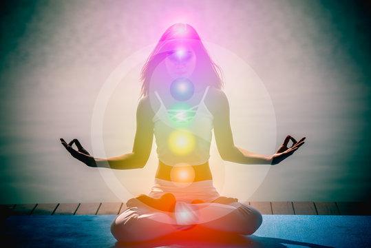 Young woman in yoga meditation with seven chakras and Yin Yang symbols.
