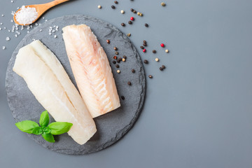 Fresh raw cod fillet with spices, pepper, salt, basil on stone plate, horizontal, copy space, top view