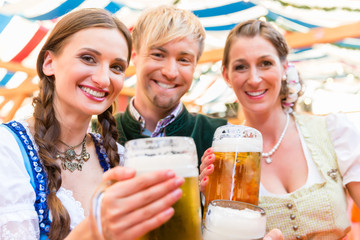 Three friends at Bavarian folk fair clinking beer glasses in tent