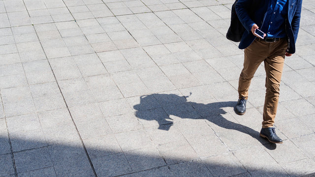 Business man walking and texting on his mobile phone on pedestrian with black silhouette shadow on ground.