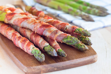 Healthy appetizer, green asparagus wrapped with bacon on wooden board, horizontal
