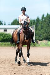 Teenage girl equestrian riding horseback on arena at sport training