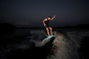 Young man riding on the wakeboard in the night