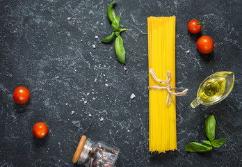 Bundle of Italian spaghetti pasta tied with string lying on dark stone background. Top view and copy space