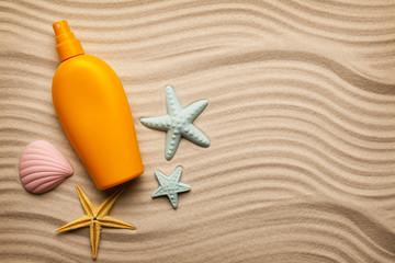 Suntan oil in a yellow bottle and seashells on the beach