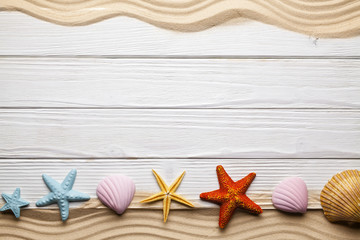 Seashells, beach sand and wooden planks
