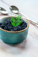 Black lumpfish caviar in a small pot