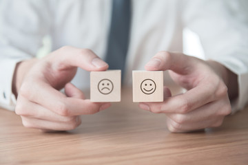Close up smiley face icon and blurred sad on wood cube, Service rating, satisfaction concept.