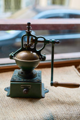 Old vintage coffee mill on a brown sackcloth in a cafe