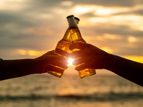Couple hands holding beer bottles and clanging on the sunset beach. Party, Holiday, Summer, Friendship Concept.