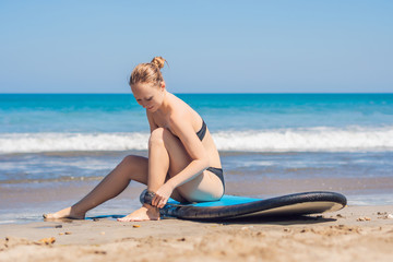Young woman surfer getting on the surfboard's leash