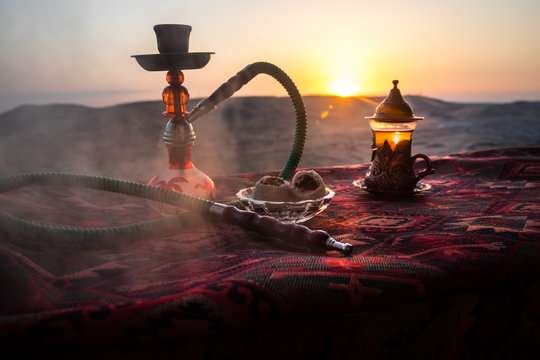 Hookah hot coals on shisha bowl making clouds of steam at desert outdoor. Oriental ornament on the carpet eastern tea ceremony. Stylish oriental shisha on sunset background.