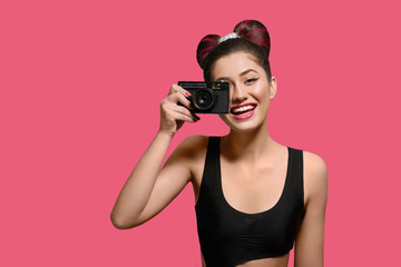 Front view of smiling, happy girl taking photo with old camera. Laughing, keeping camera, having fancy hairstyle with a bow, colorful day make up with pink lipstick. Posing on bright pink background.