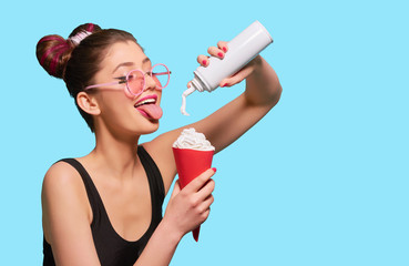 Fancy girl pressing whipped cream in red paper can. Posing with pipped tongue, smiling, wearing black tshirt, pink eyeglasses, pretty, cute hairstyle. Keeping white bottle. Blue studio background.
