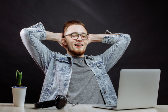 young handsome man has finished using the laptop. office worker relaxing and locking arms behind head
