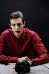 close up portrait of handsome guy in red shirt looking at the camera