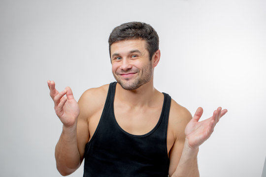 young funny man is pulling a faces with raised hands. draw face. bad actor. male is making a show that he is indifferent to the problem
