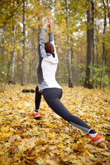 Autumn image from back of sports woman stretching at forest