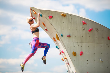 Photo from side of sports woman in leggings hanging on wall for climbing against blue sky