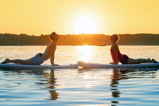 young sexy woman girl family are doing yoga on an sup board at a lake sea water